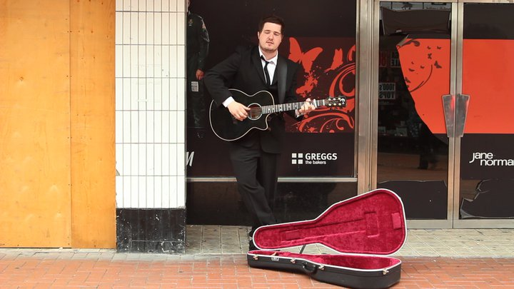 Danny Gruff performing outside Woolworths in the video for Wanderlust
