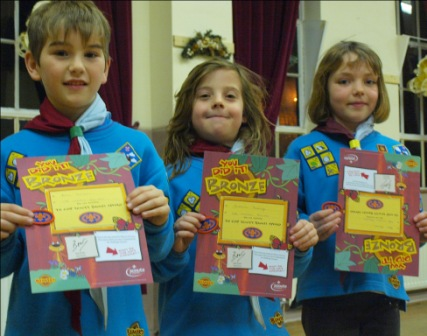 Beaver Scouts Kian Razavi, Cameron Rammage and Eleri Davies with their Bronze Chief Scouts Awards signed by Bear Grylls