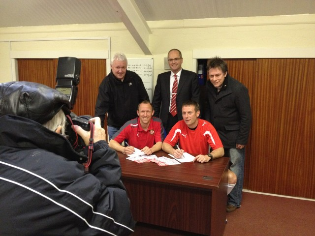Andy Morrell and Billy Barr sign a new contract with Wrexham FC. Picture behind them from L-R are Wrexham Supporters Trust Chairman Peter Jones, Wrexham FC CEO David Roberts and WST board member Tom Stanford.